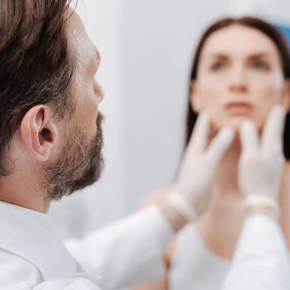 Elevation Med Spa Lone Tree Colorado - Kybella service offers a variety of benefits, medical professional assessing woman's face prior to injections